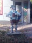 Скульптура чоловіка з келихом біля пабу